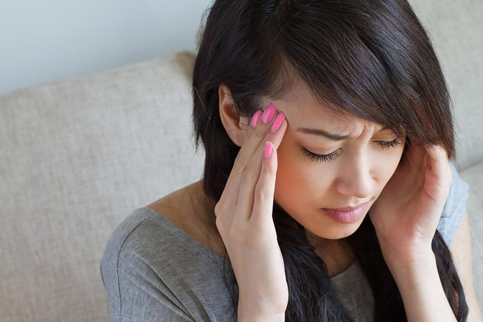 Asian woman with a headache holding her hands to her temples