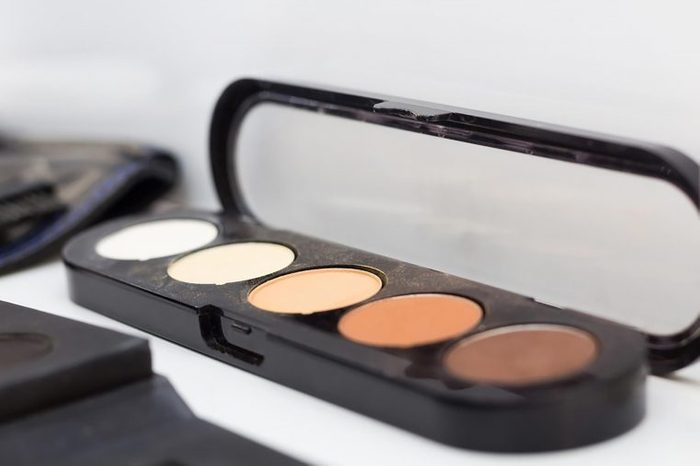 A palate of concealer in shades of brown and tan.