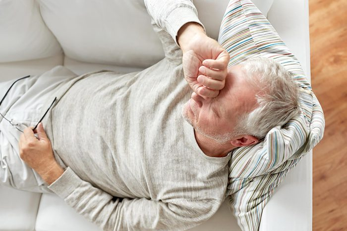 older man on couch sleeping with hand to head