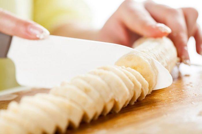 Woman slicing a banana.