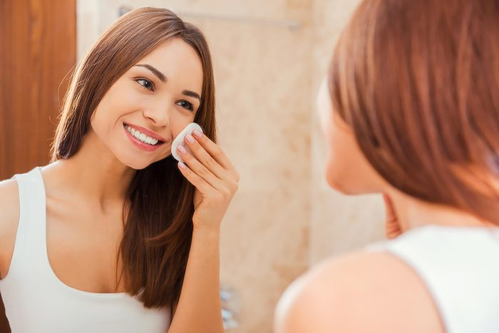 woman looking in mirror and cleaning face