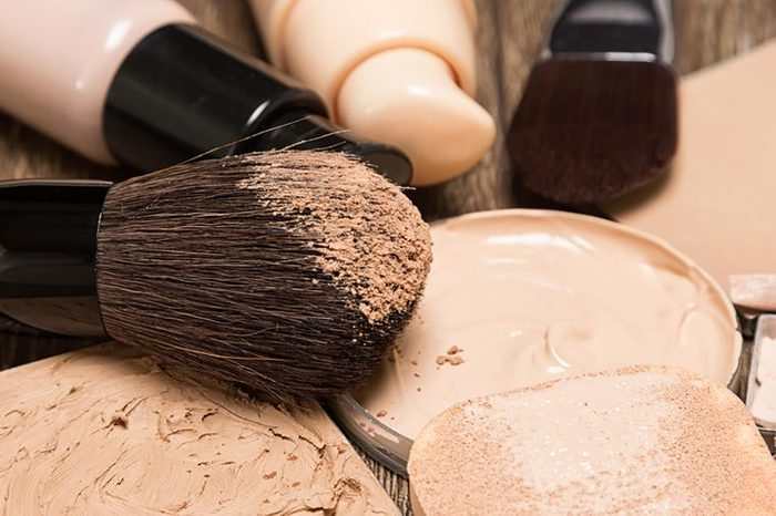 A foundation brush and jars of foundation in shades of beige.
