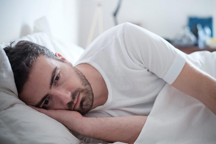 man lying on side in bed, looking sad