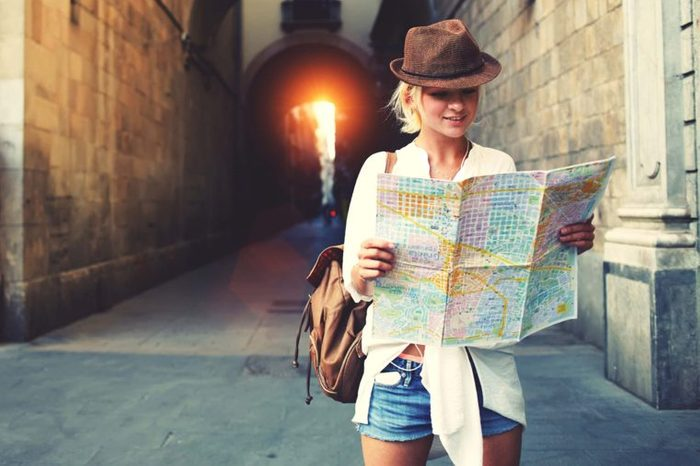 woman in jaunty hat holding map
