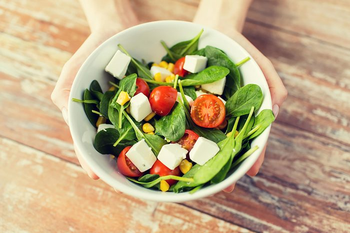 hands holding salad with tomatoes in white bowl