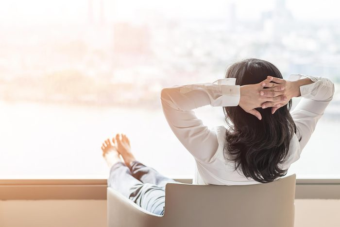 woman relaxing with hands behind head and looking out window