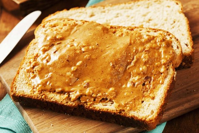 Piece of bread slathered with peanut butter