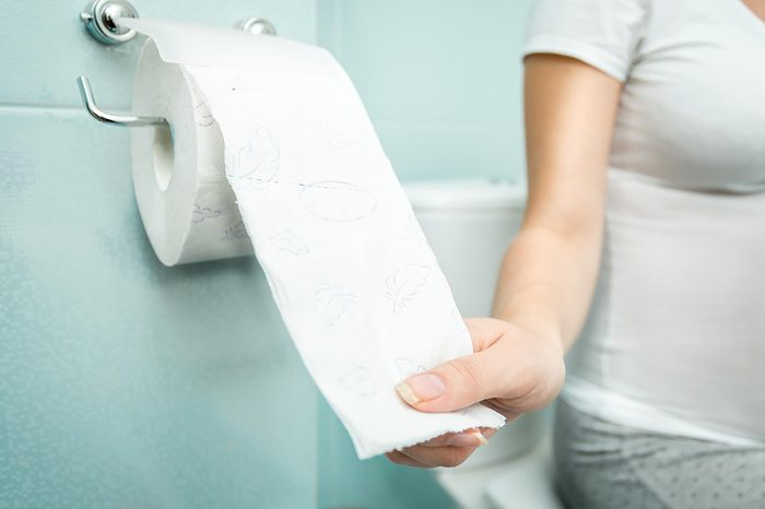 woman on toilet pulling toilet paper