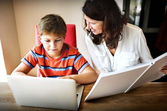 Woman helping boy with homework