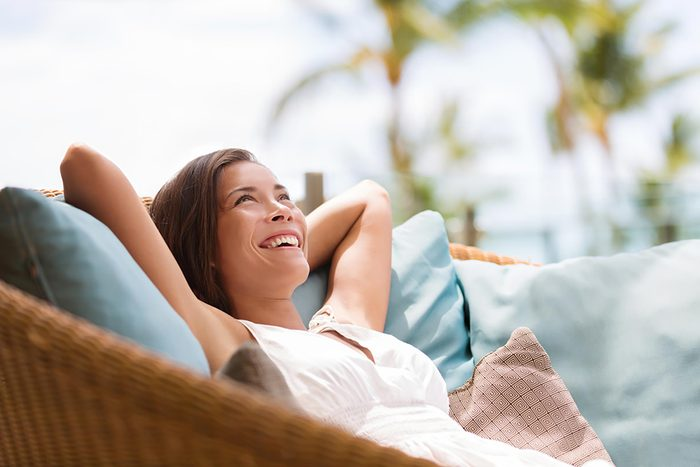 happy woman relaxing on pillows outside