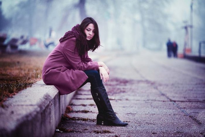 Sad woman sitting outside