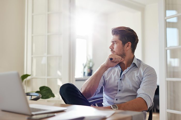 man looking out window while sitting at computer