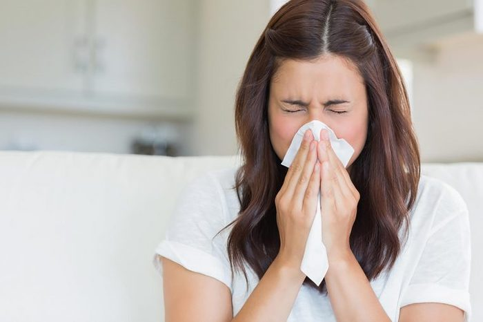 brunette woman sneezing into a tissue