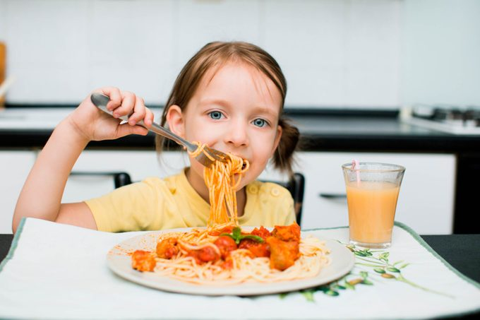 young girl eating spaghetti with meatballs and orange juice
