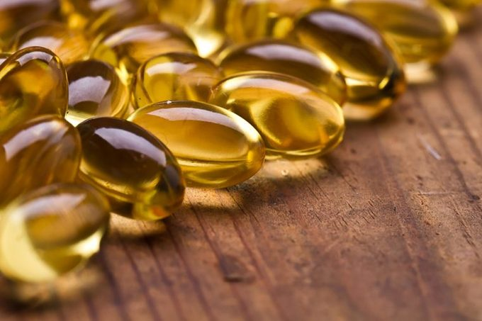 Omega 3 fatty acid capsules on a wooden surface.