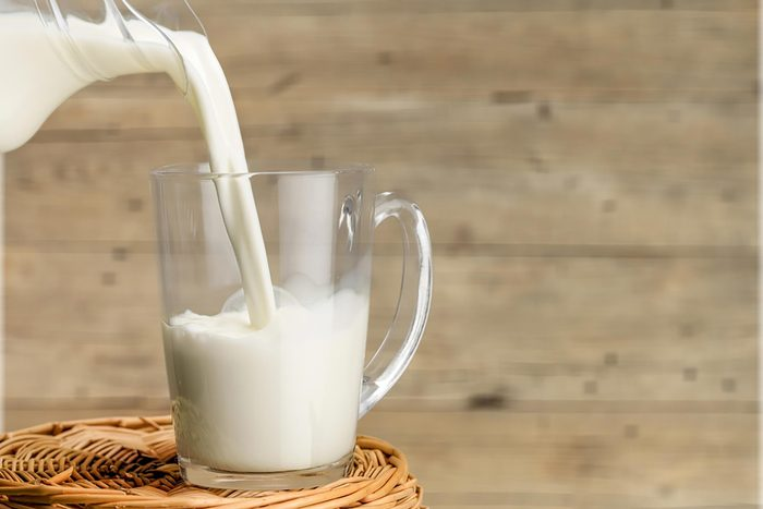 milk being poured in glass mug