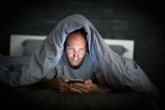man under bed covers looking at phone