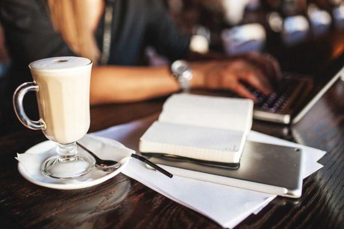 desk with coffee mug, notebook, laptop