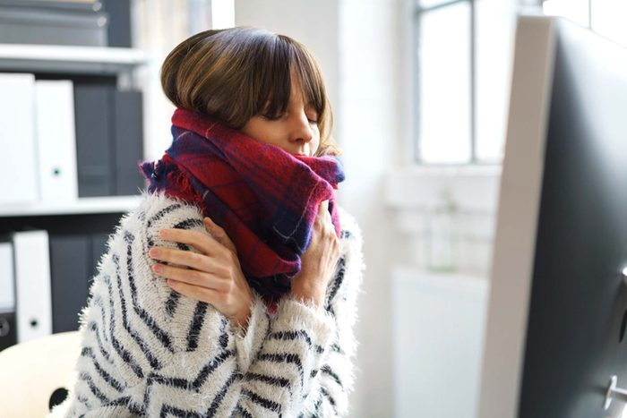 woman indoors wrapped in a scarf, chilled