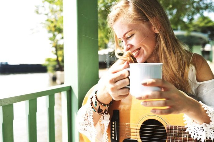 Woman with mug and guitar on a porch