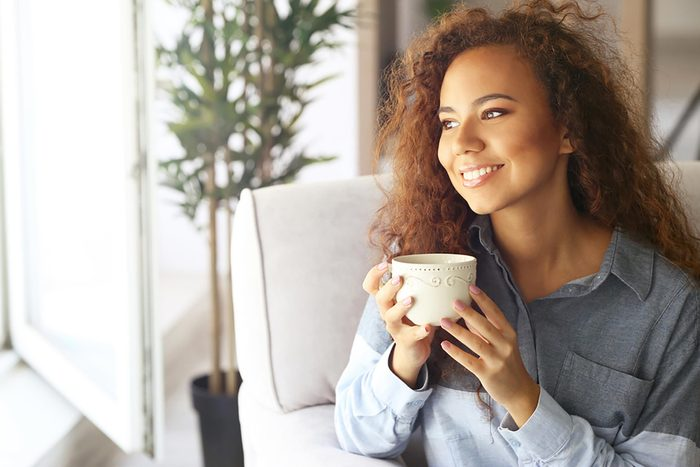 woman staring out a window and smiling with a coffee