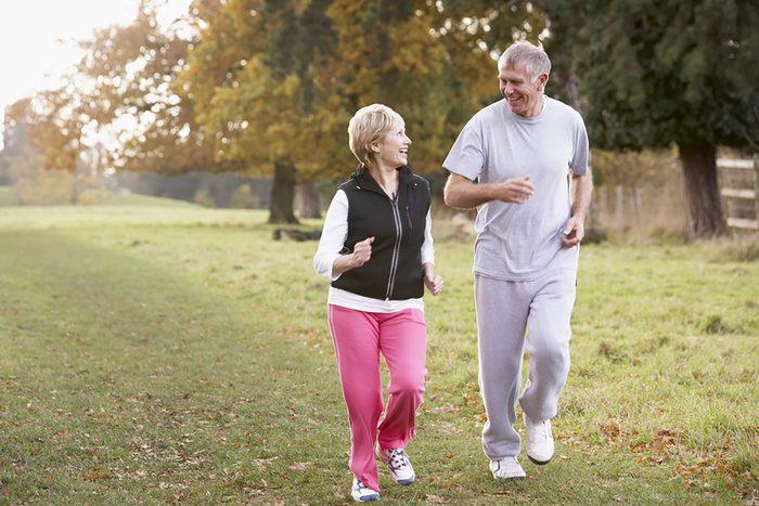 Elderly couple walking outdoors in a field