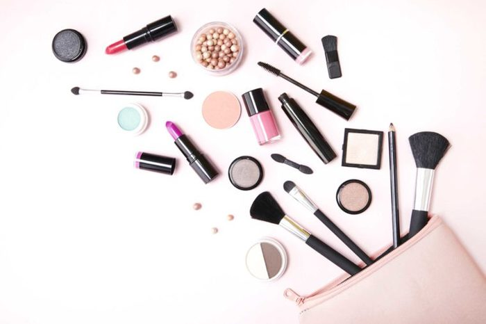 Makeup bag with makeup products spilling out onto a surface.