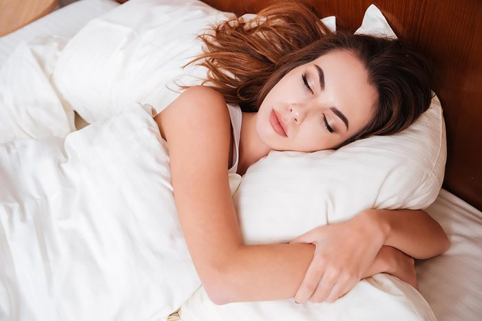 woman sleeping, hugging her pillow