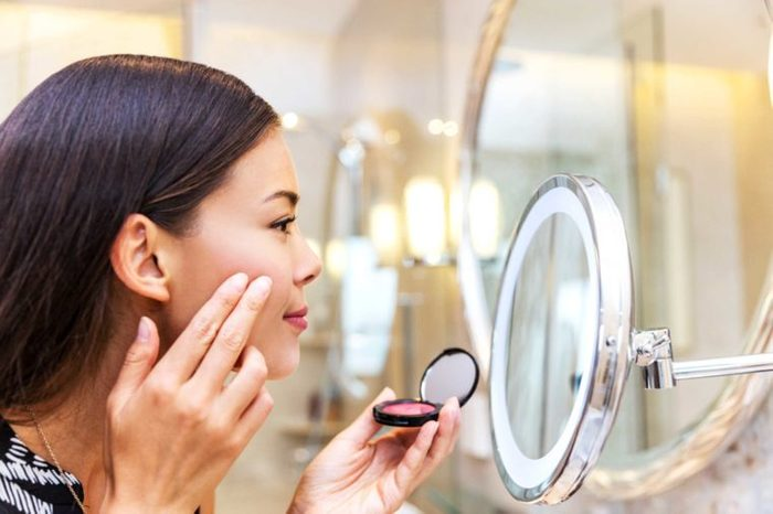 Asian woman applying makeup in a mirror