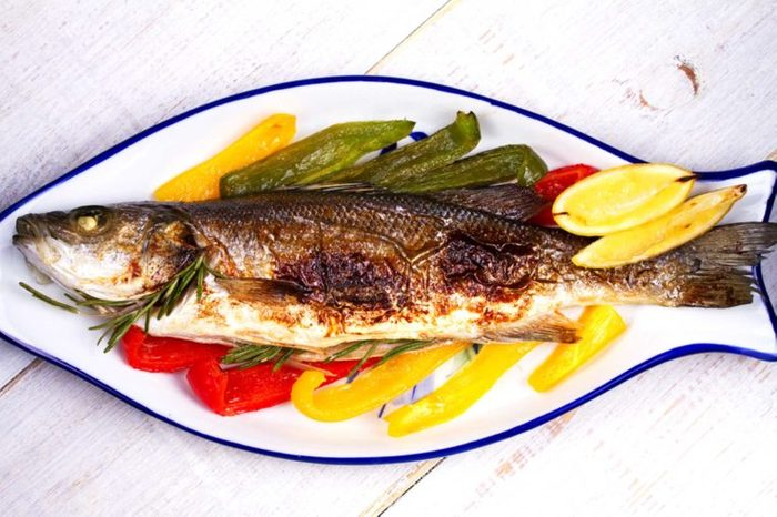 cooked fish on a serving platter with bell peppers