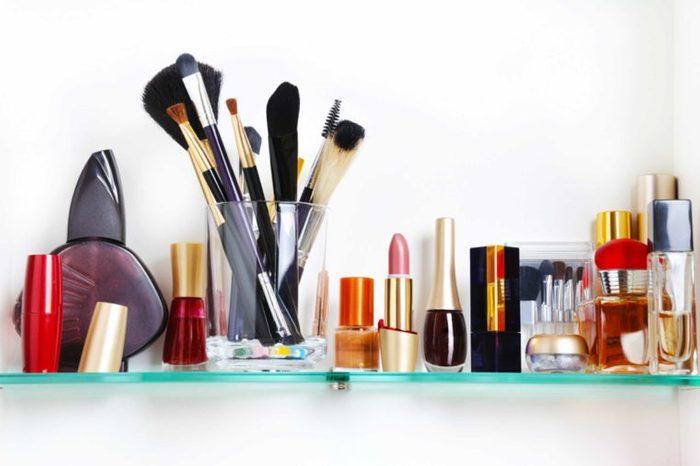 Row of makeup in the bathroom medicine cabinet.