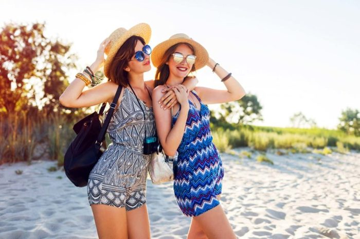 Two girlfriends hitting the beach wearing wide-brim hats and sunglasses.