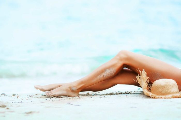 a woman's legs reclining on a beach
