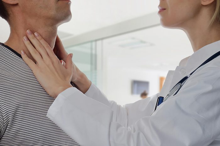 man getting thyroid checked by doctor
