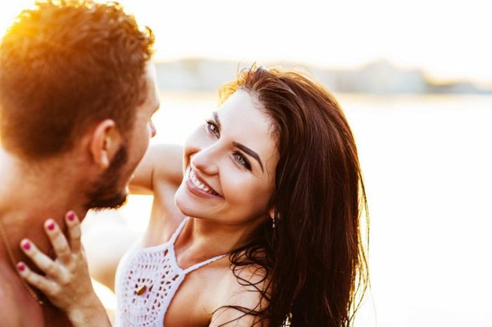 woman with brunette hair looking into a man's eyes
