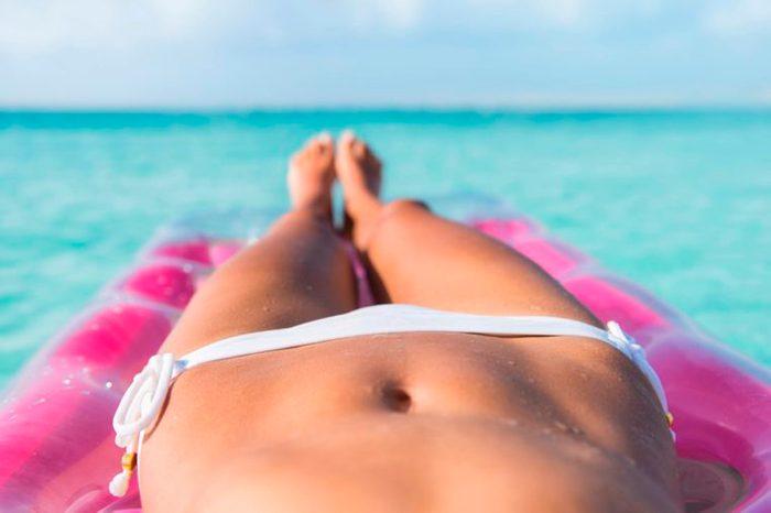 woman in a bikini sunbathing on a raft
