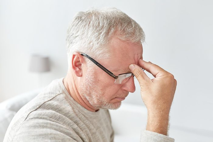 stressed older man with hand on forehead