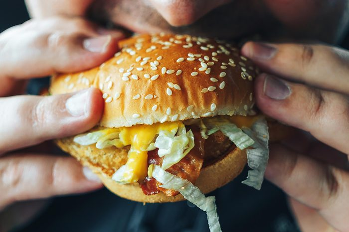 person eating chicken sandwich