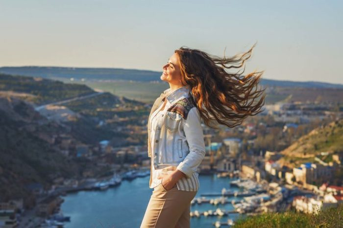 woman smiling on the top of a hill with a nice view