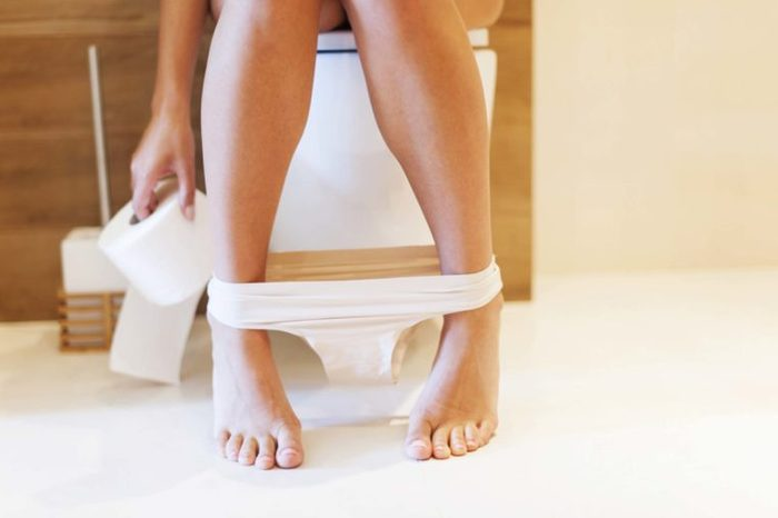 woman's legs while on toilet, underwear around her ankles