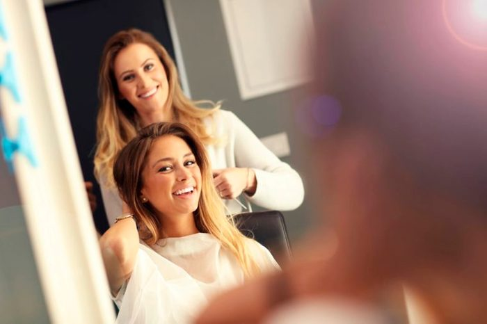 stylist working on woman's hair, looking in mirror