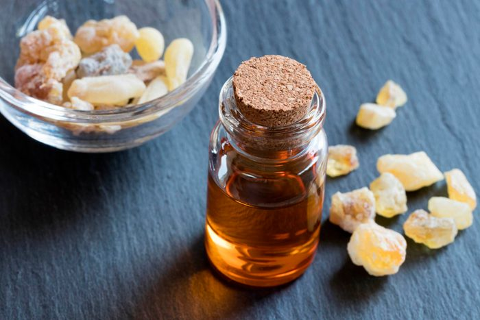 candied ginger on a table with essential oil bottle
