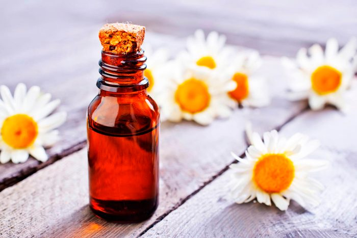 bottle of chamomile oil with blossoms