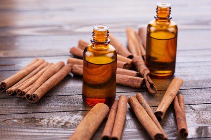 cinnamon oil and cinnamon sticks on a wooden table