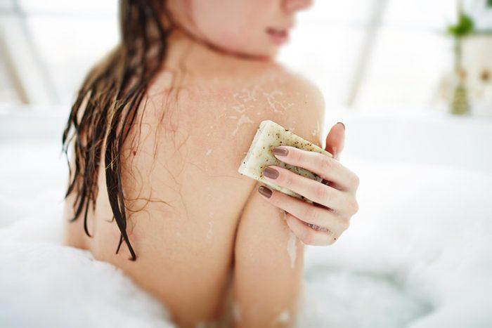 Woman using soap in a bubble bath.