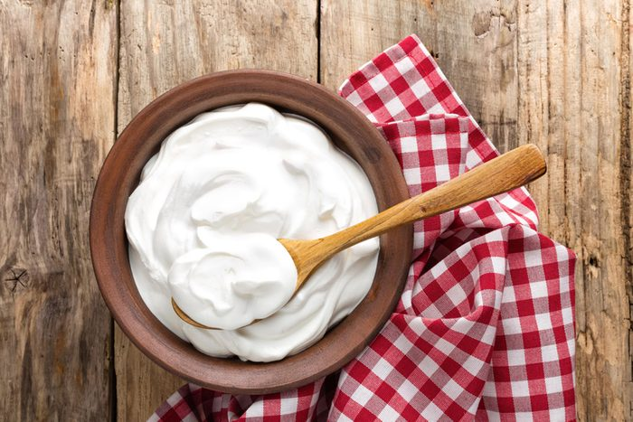 wooden bowl filled with yogurt with a wooden spoon