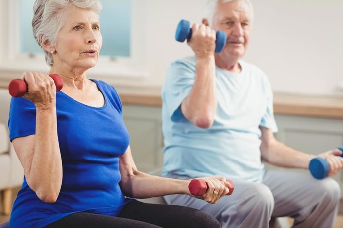 two older people lifting weights
