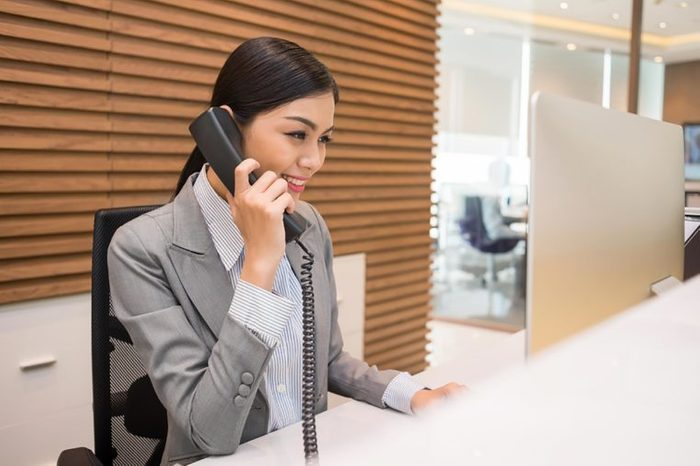 Asian woman in an office speaking on a phone