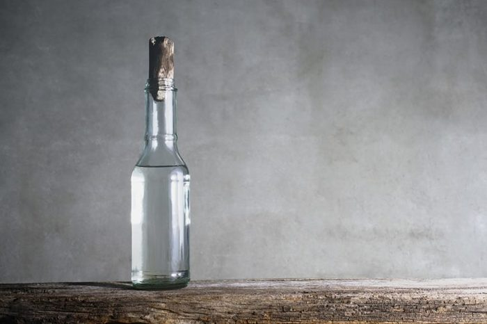 vinegar in a corked, clear glass jar on a wooden surface