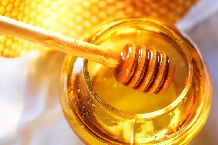 honey jar with a wooden honey dipper